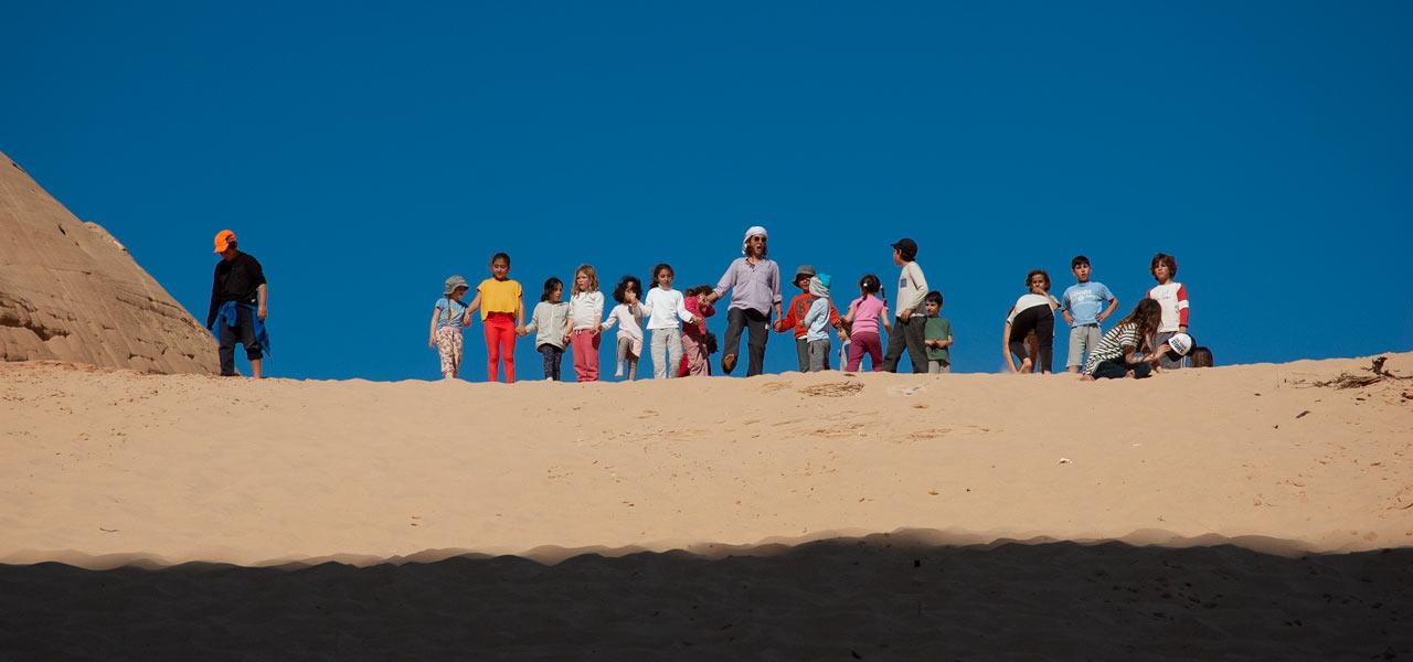 ילדים ומורה עומדים בראש דיונה לקראת ריצה למטה