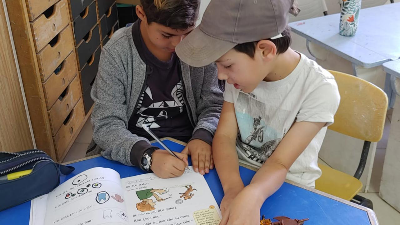 שני תלמידים לומדים בכיתה עם חוברת עבודה
