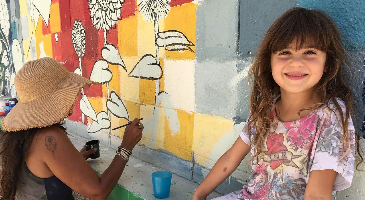 ילדה מחייכת למצלמה ליד אישה שמציירת על קיר